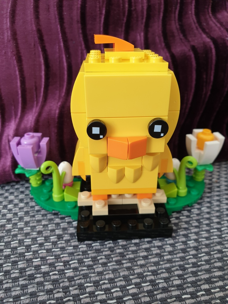 A yellow chick made out of Lego. A purple and a white Lego flower are built and stood one at each side.
