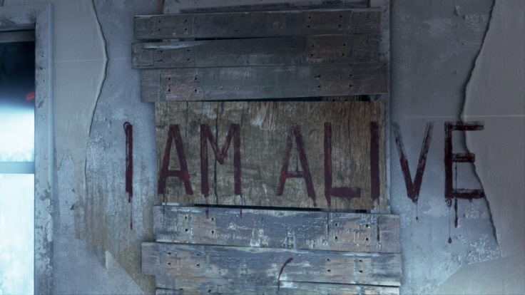 I am alive written on a wall in capital letters.