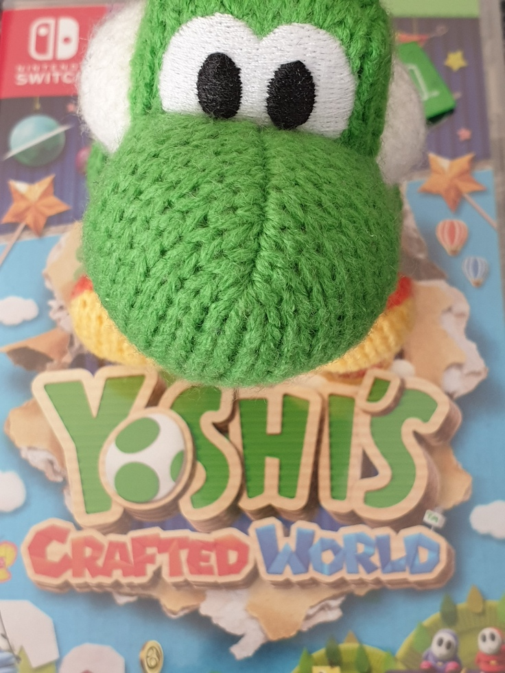 A woolly Yoshi amiibo sits on top of the Yoshi's Crafted World game box.