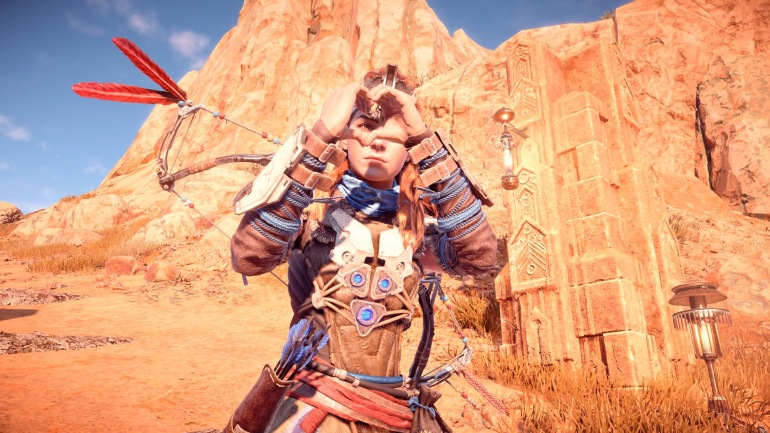 Aloy from Horizon Zero Dawn holds her hands together in a heart shape as you can see her eye through the centre of the heart.  The sky is blue, and there are rocks and lamps in the background.