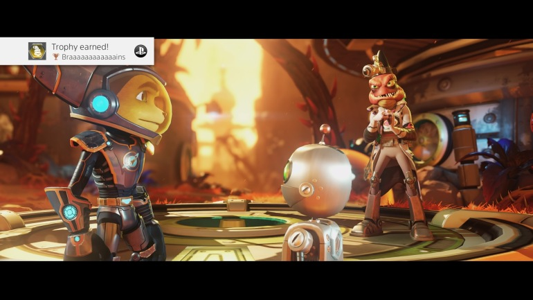 "The ""Brains"" trophy screenshot from Ratchet and Clank PS4 game.  It has Ratchet and Clank facing each other with the scientist NPC in the background."
