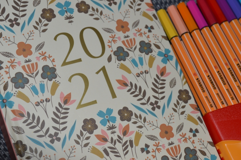 A 2021 planner with gold numbers and a floral pattern is next to some coloured fine line pens.