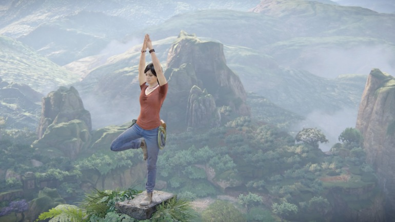 Chloe taking some time to do some yoga on top of a peak.  She stands on one leg with the other bent so her foot is above her knee. Her hands are joined and arms stretched above her head.